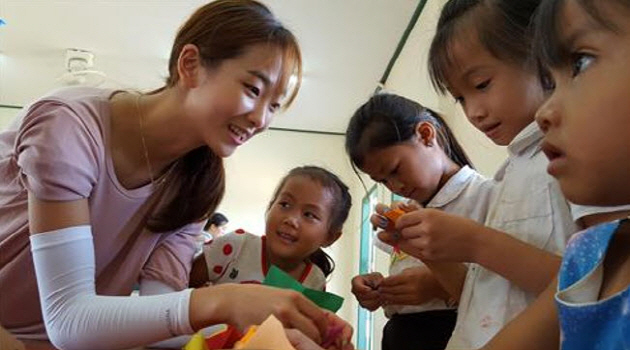 A student at the College of Education is teaching Laos children in Xiangkhouang